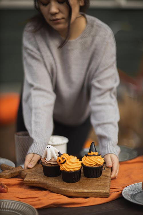 Woman in Gray Sweater Holding Cupcakes