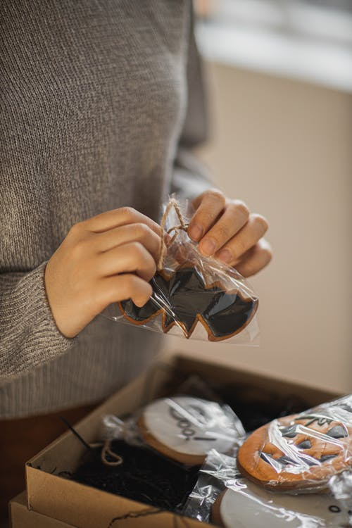 Person in Gray Sweater Holding Brown Plastic Pack with Cookies