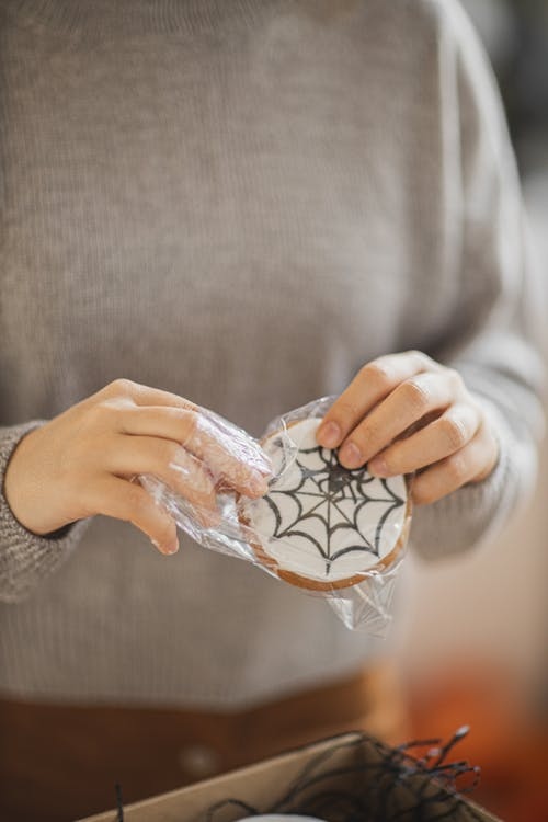 Person in Gray Long Sleeve Shirt Holding a Cookie