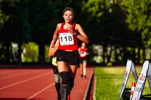 Concentrated ethnic sportswoman running on race track during competition