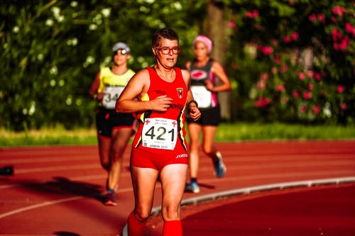 Sportswoman with unrecognizable competitors running on track in stadium