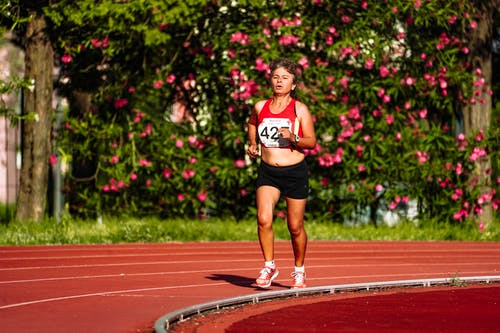 Middle aged female athlete in sportswear running during track and field competition while looking forward