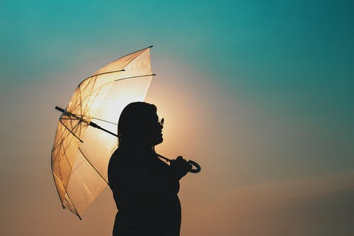 Silhouette of Man Holding Umbrella during Sunset