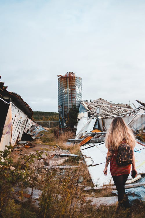 Back view of anonymous female with backpack strolling along damaged wall with remains of broken construction with rusty tank in distance