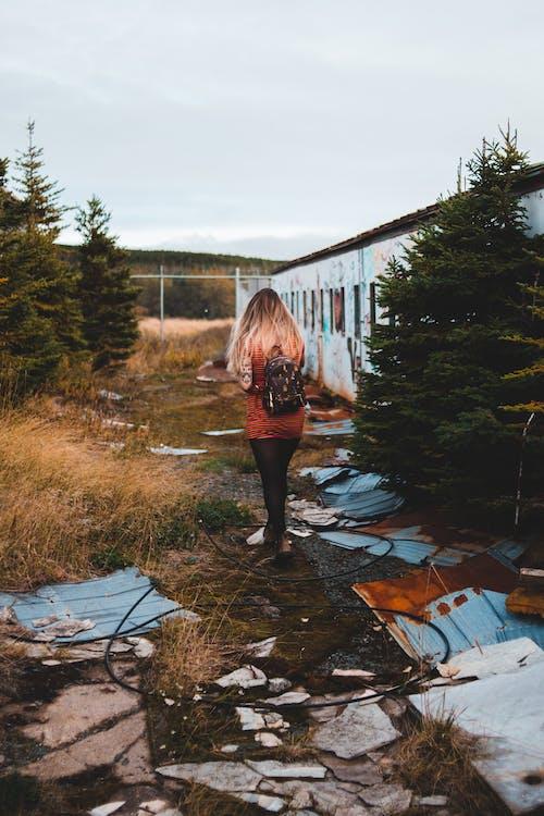 Unrecognizable woman walking near abandoned house