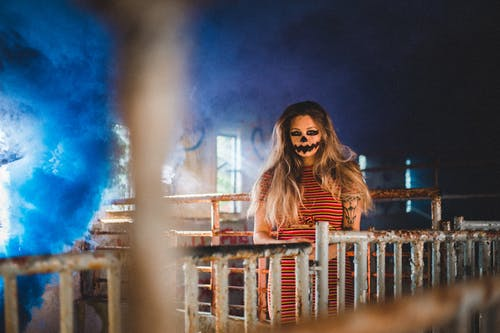 Woman with scary makeup standing near metal fence