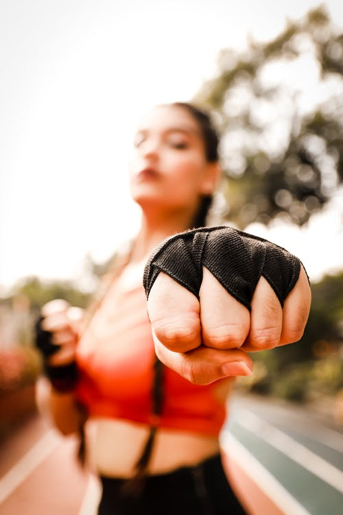 Young strong female in sportswear standing on racetrack and showing punch with fists in stadium in summer day