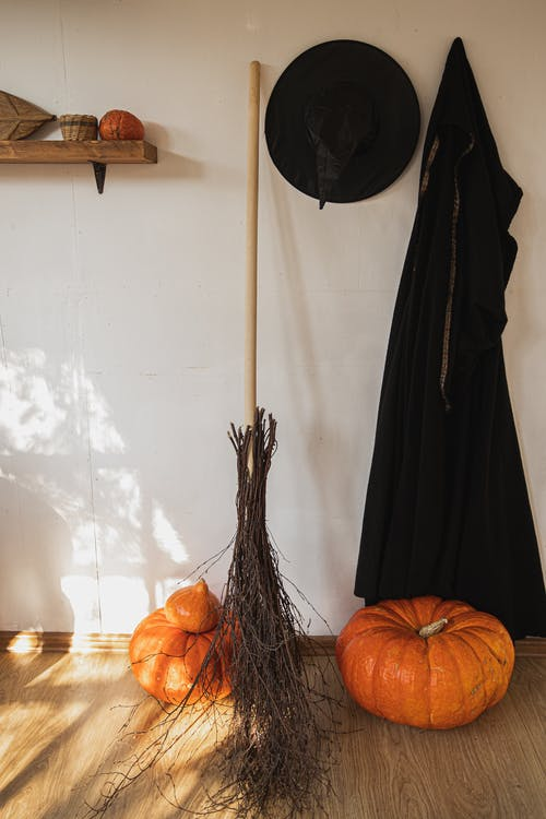 Orange Pumpkin Beside Black Witch Costume and a Broom