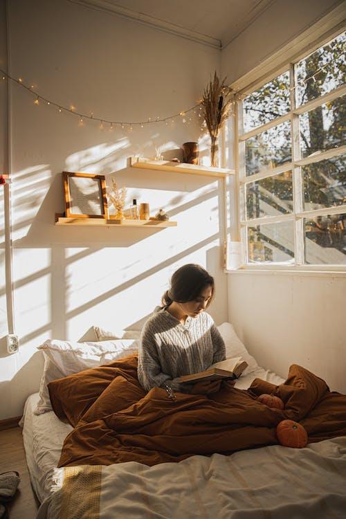 Gri Uzun Kollu Gömlekli Kadın Yatağında Kitap Okurken