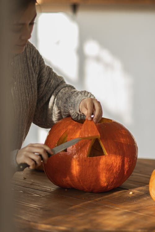Woman in Gray Long Sleeve Shirt Carving a Pumpkin