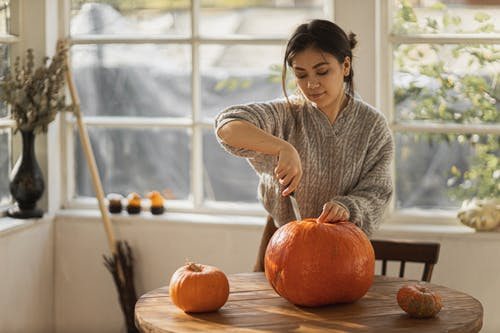 Woman in Gray Sweater Carving Orange Pumpkin