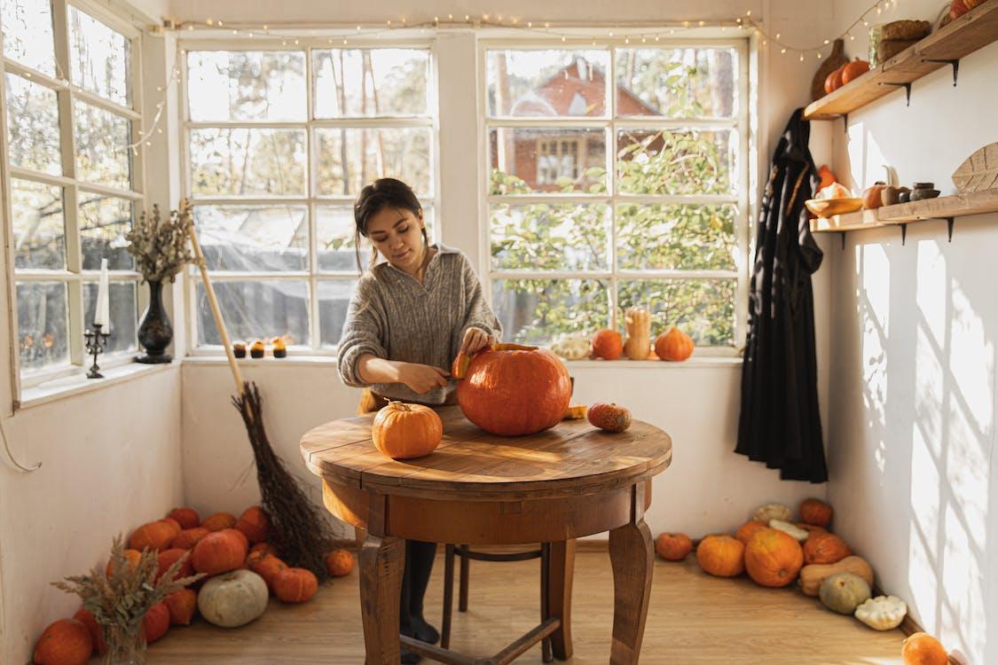 Woman in Gray Long Sleeve Shirt Carving a Big Orange Pumpkin