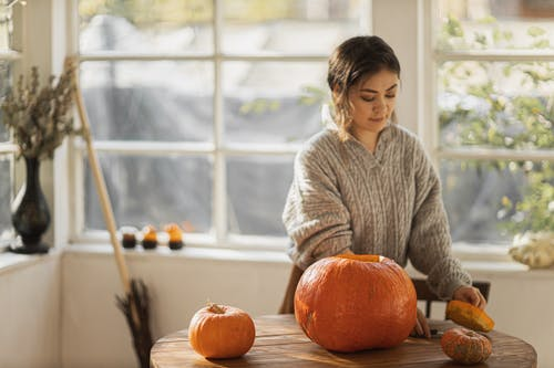 Woman in Gray Sweater Standing Near Brown Wooden Table With Pumpkin