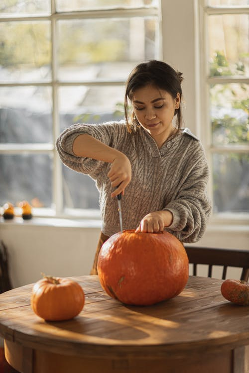 Woman in Gray Long Sleeve Shirt Holding Pumpkin