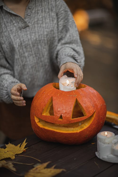 Person in Gray Long Sleeve Shirt Putting Candle in the Jack O Lantern