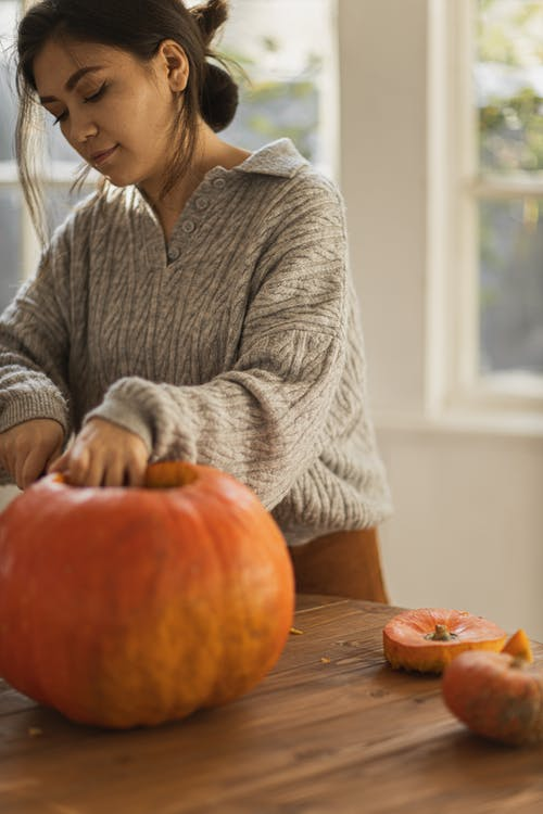 Woman in Gray Long Sleeve Shirt Holding Orange Pumpkin