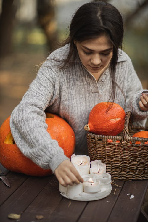 Woman in Gray Long Sleeve Shirt Lighting the Candles