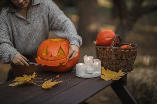 Person in Gray Sweater Holding Jack O Lantern