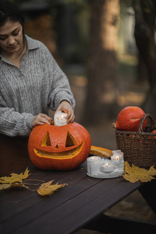 Woman in Gray Sweater Holding Pumpkin