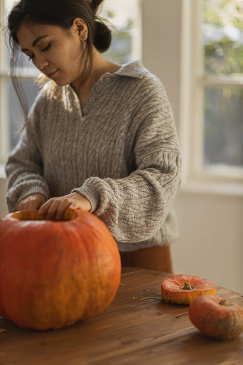 Woman in Gray Sweater Holding Big Pumpkin