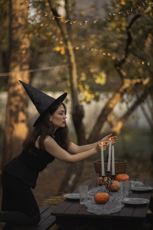 Woman in Black Sleeveless Dress Wearing Black Hat Lighting The Candles