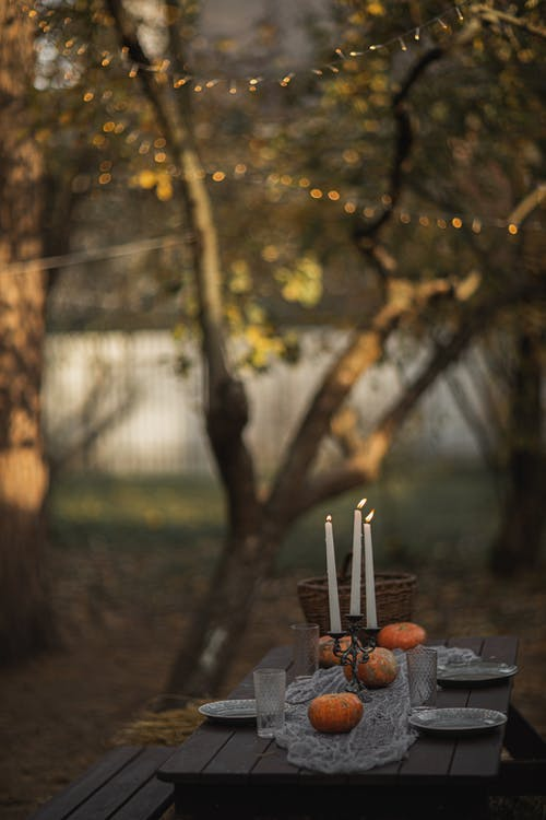 Halloween Table Setting With Lighted Candles And Pumpkins