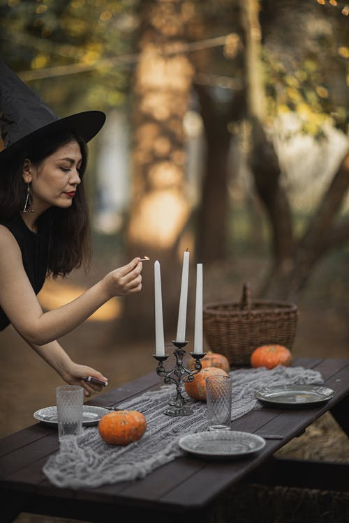 Woman in Black Witch Costume Lighting A Candle On Table
