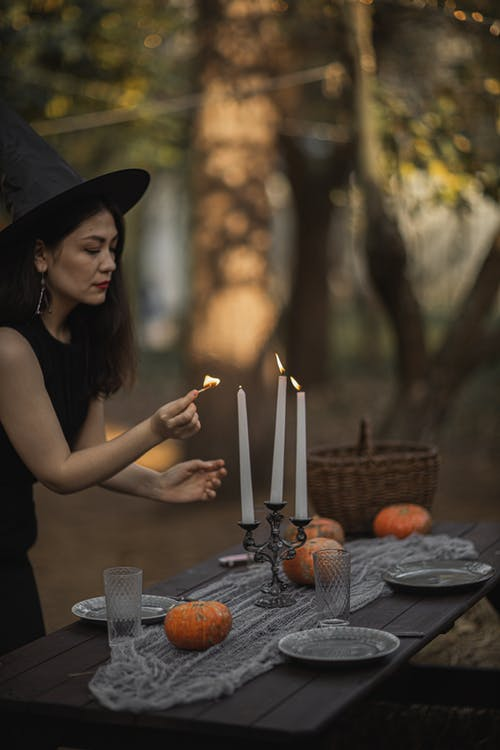 Woman in A Witch Costume Lighting Candles On The Table