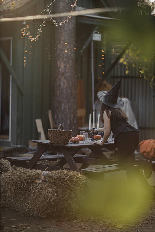 Woman Wearing Black Witch Hat Setting the Table