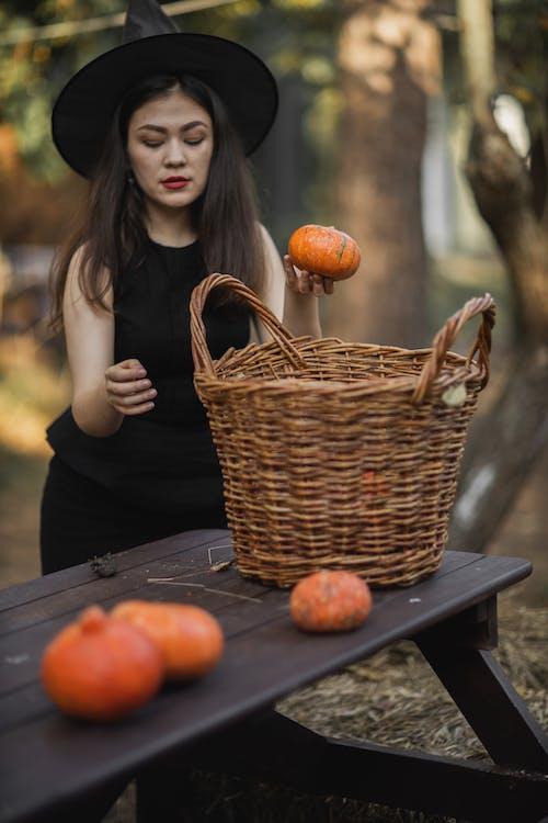 Woman in Black Dress Holding Pumpkin Beside Brown Woven Basket