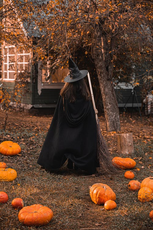 Woman in A Witch Costume With Pumpkins On The Ground