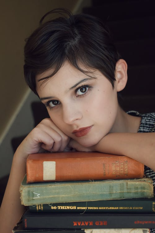 Woman in Black and White Shirt Leaning on Books