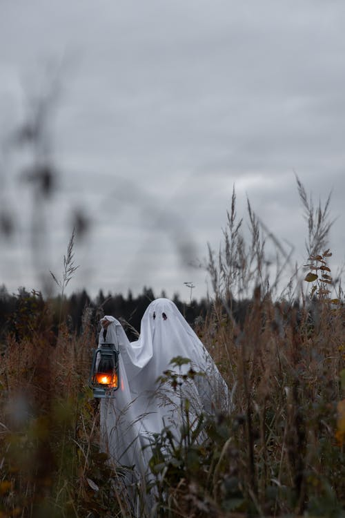 Person Wearing A Ghost Costume With A Lantern