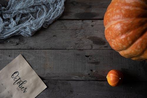 Pumpkin Beside A Gray Yarn on Brown Wooden Table