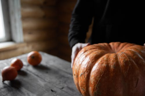 Person Holding Orange Pumpkin on Gray Wooden Table