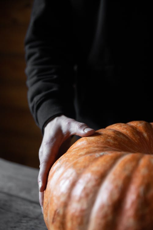 Person Holding A Pumpkin on Table