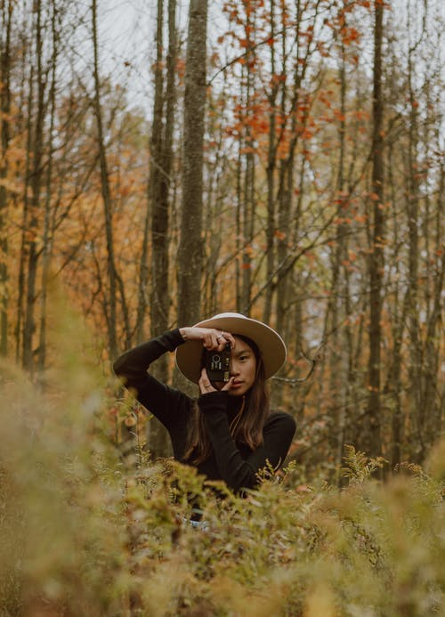 Concentrated young ethnic female traveler in elegant outfit and hat taking photo on retro film camera while relaxing in picturesque autumn forest