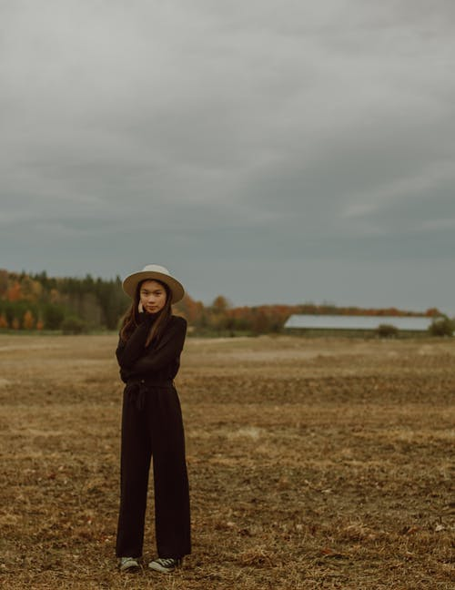 Trendy young ethnic female standing on dry rural field against overcast sky