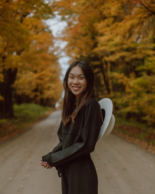 Smiling Woman Standing on a Dirt Road