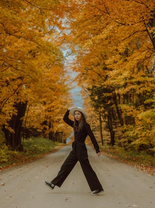 Женщина в черной куртке и черных штанах идет по дороге между деревьями