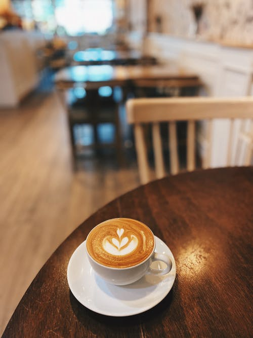 White Ceramic Cup on White Saucer on Brown Wooden Table