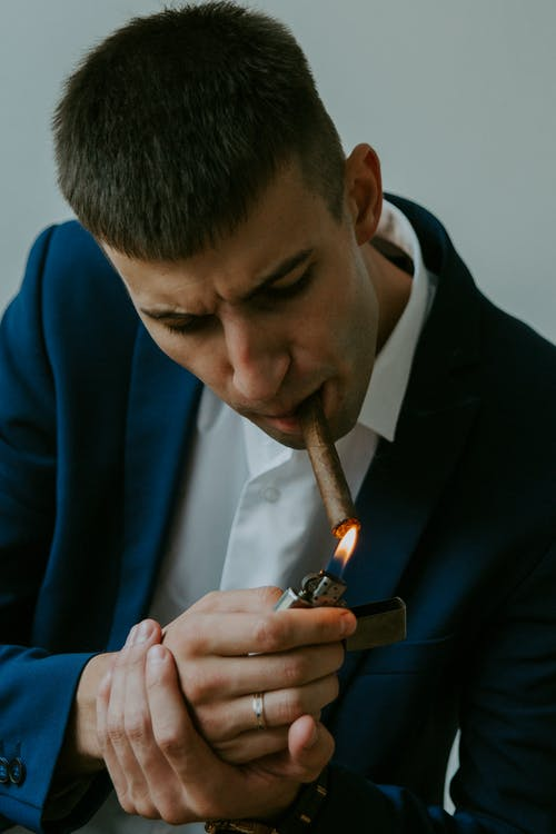 Man in Blue Suit Holding Black Disposable Lighter
