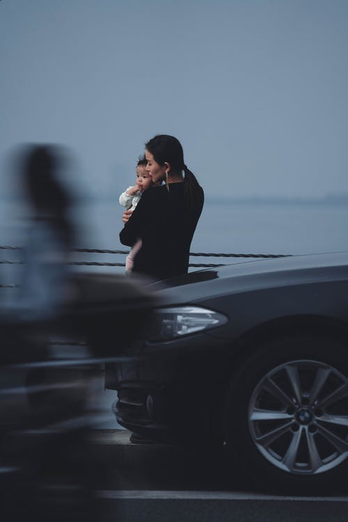 Back view calm young female in black wear holding little baby on hands while standing embankment near moving cars