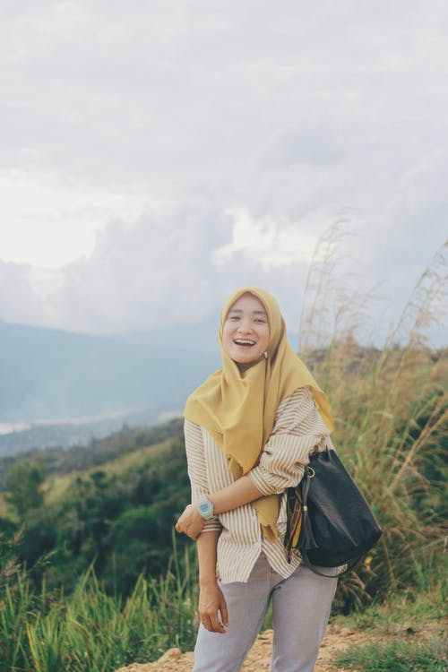 Woman in Beige Hijab and Black Leather Jacket Standing on Top of Mountain