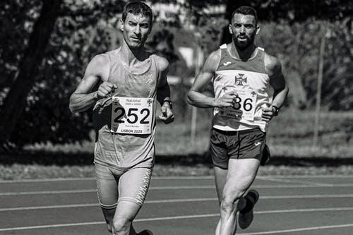Black and white of concentrated sportsmen in active wear with numbers running on race track during athletic contest