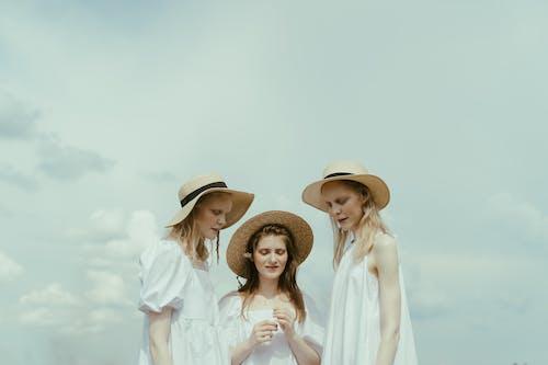 2 Women in White Dress Shirt Wearing Brown Straw Hat