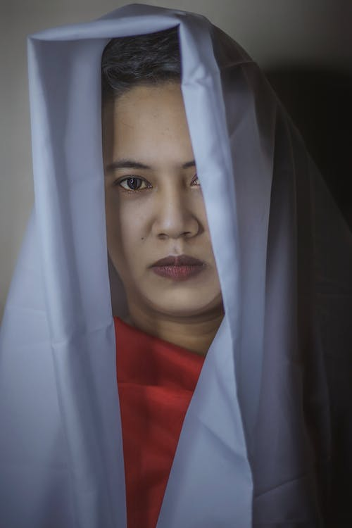 Serious ethnic young lady covering head with white cloth and covering breast with red fabric while looking at camera in light studio