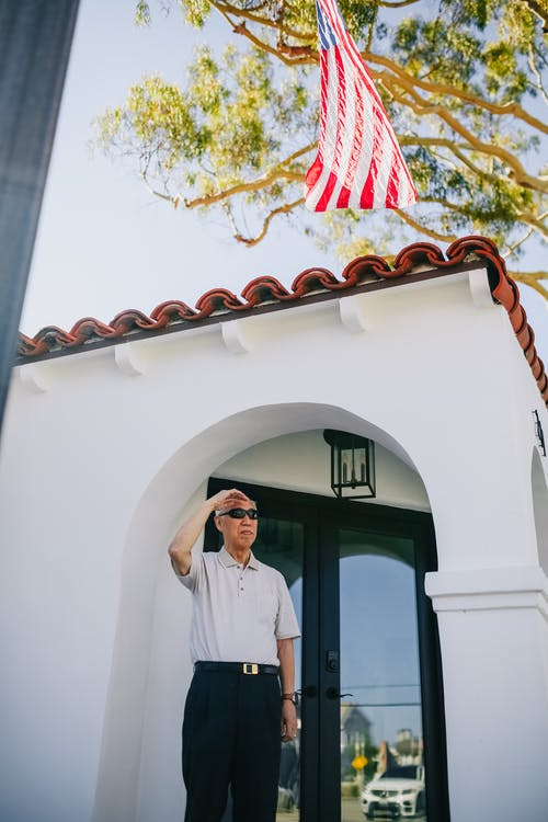 Man in White Button Up Shirt Standing Beside White Concrete Building