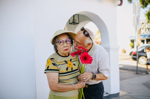 Old Man Kissing Her Wife While Giving A Bouquet Of Flowers