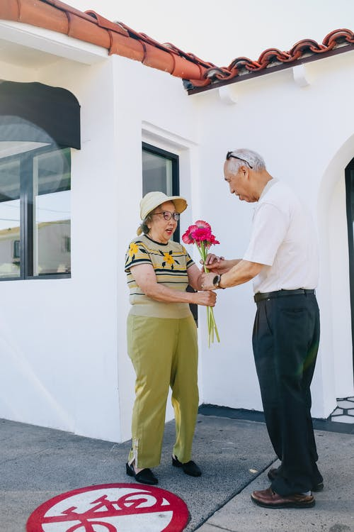 Elderly Man Giving Red Flowers to His Wife